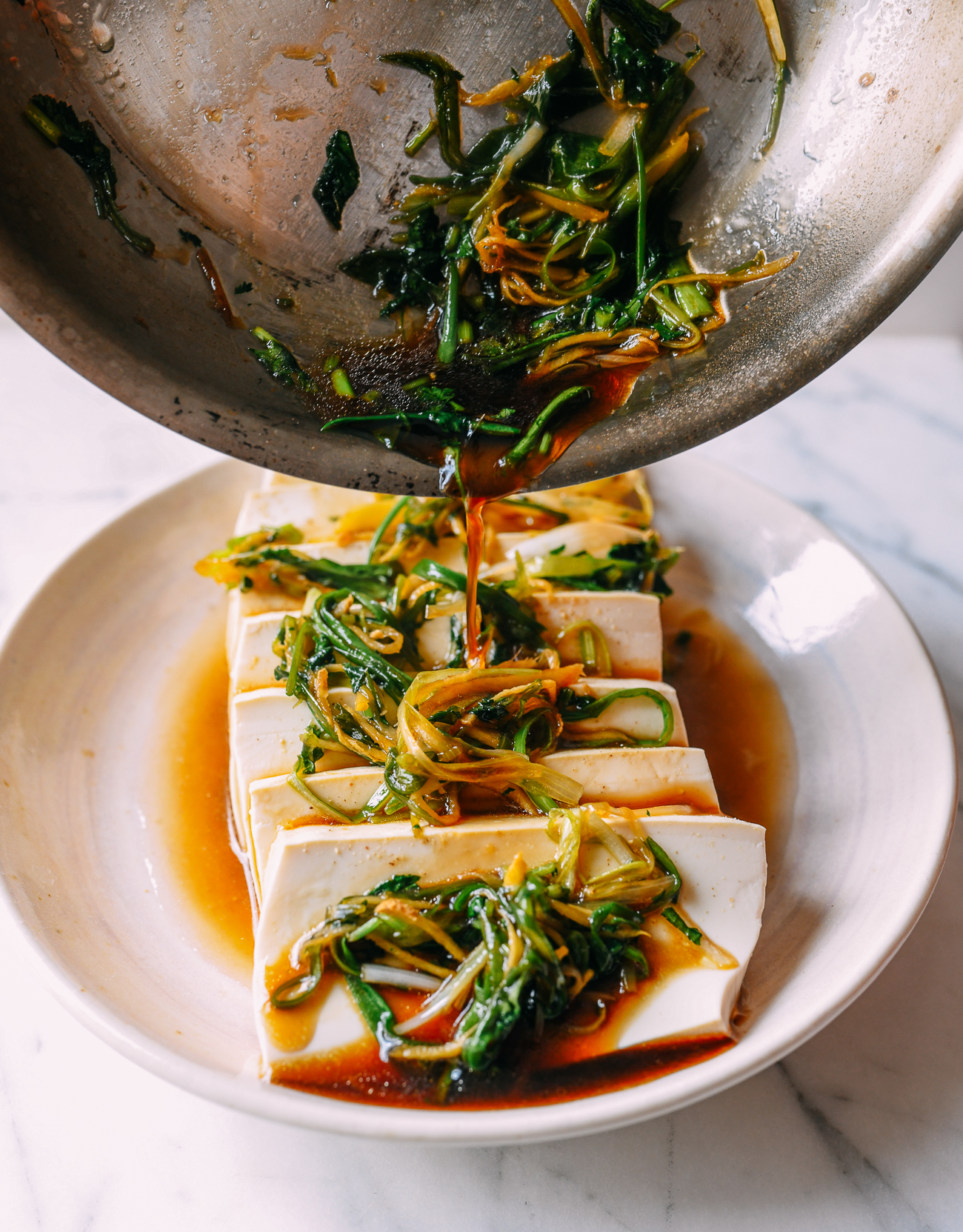 Pouring sauce over tofu