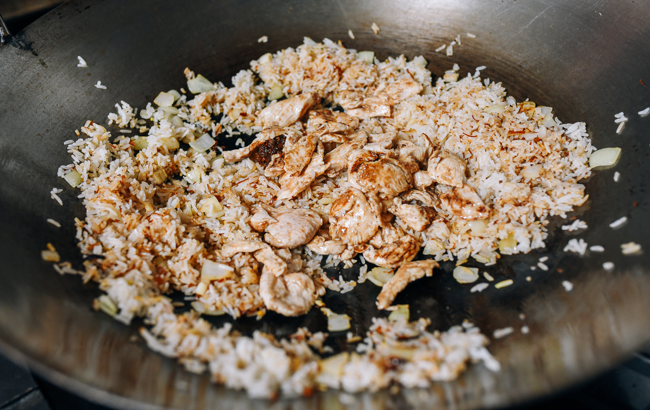 Adding cooked chicken to rice in wok