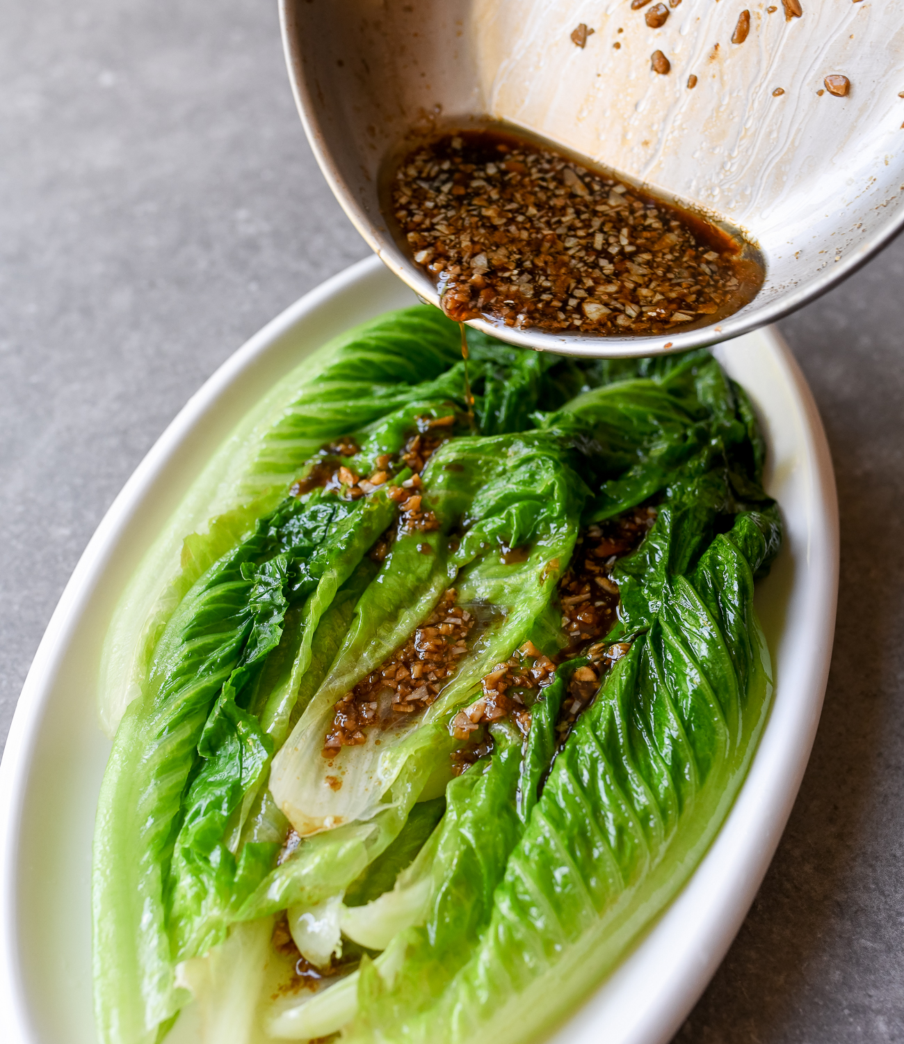 Pouring sauce over blanched romaine lettuce leaves