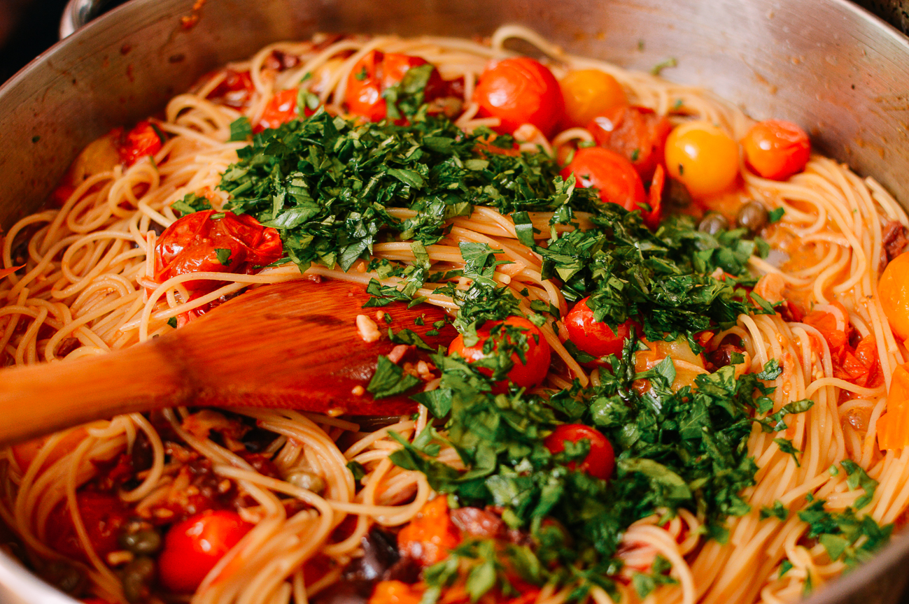 Tossing together spaghetti with roasted tomatoes and chopped parsley