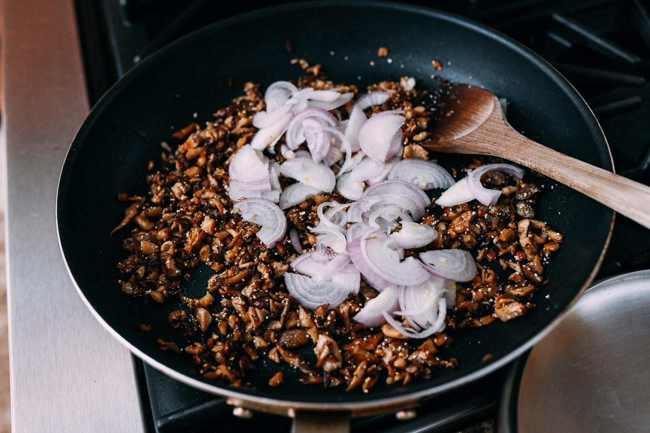 Adding shallots to pan of mushrooms