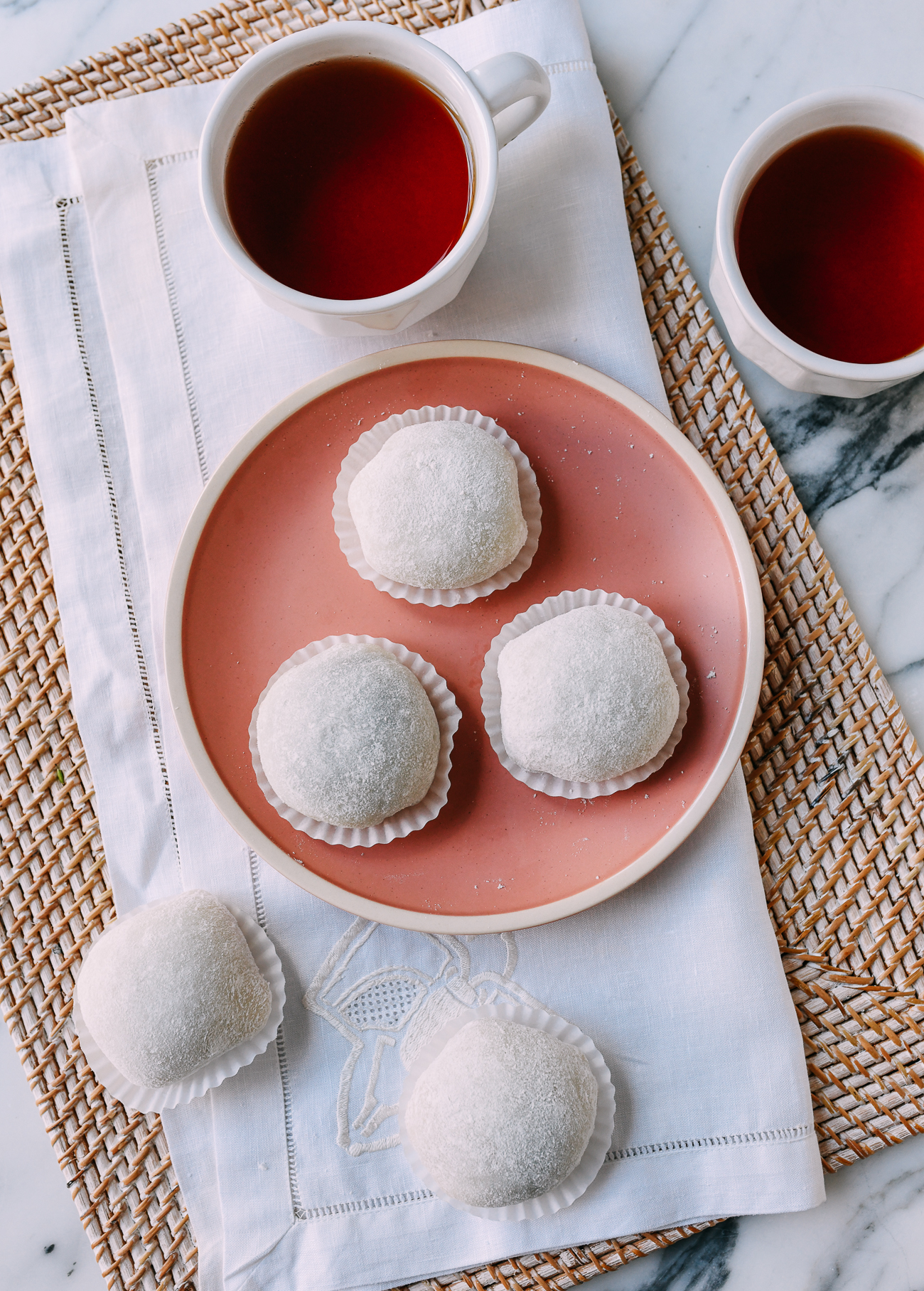 Mochi balls in paper cups on pink plate