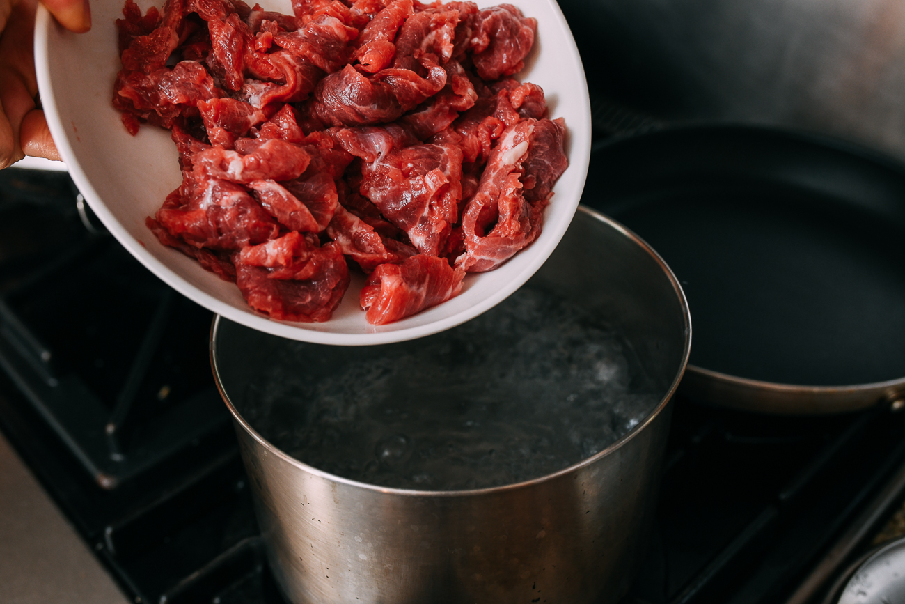 Adding marinated beef slices to boiling water