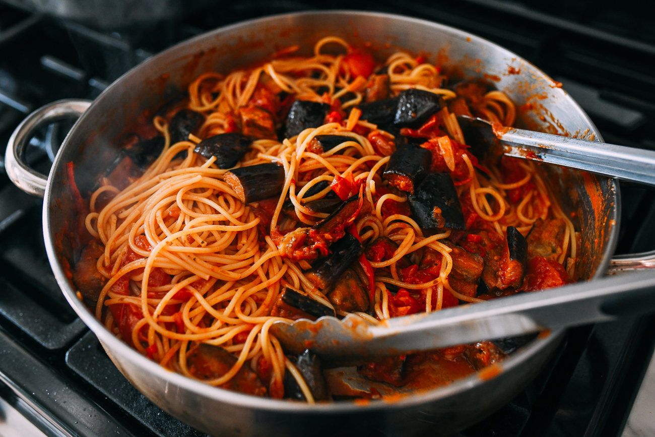 Tossing pasta alla norma in pan
