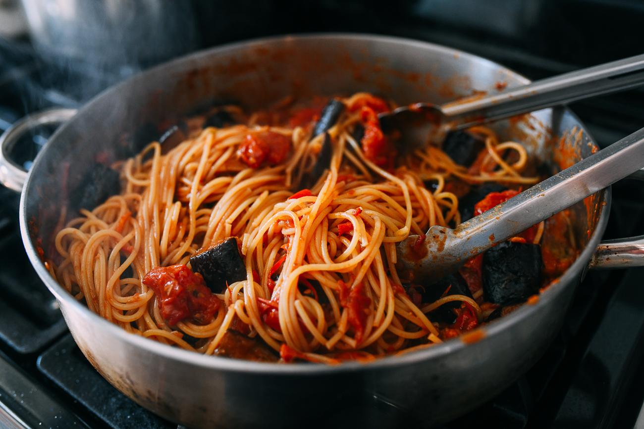 Tossing pasta alla norma in skillet