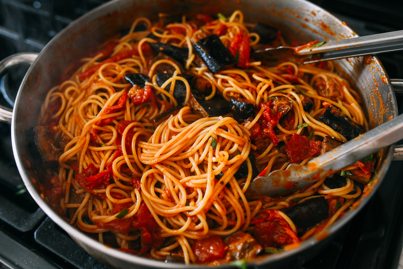 Tossing pasta alla norma together before serving