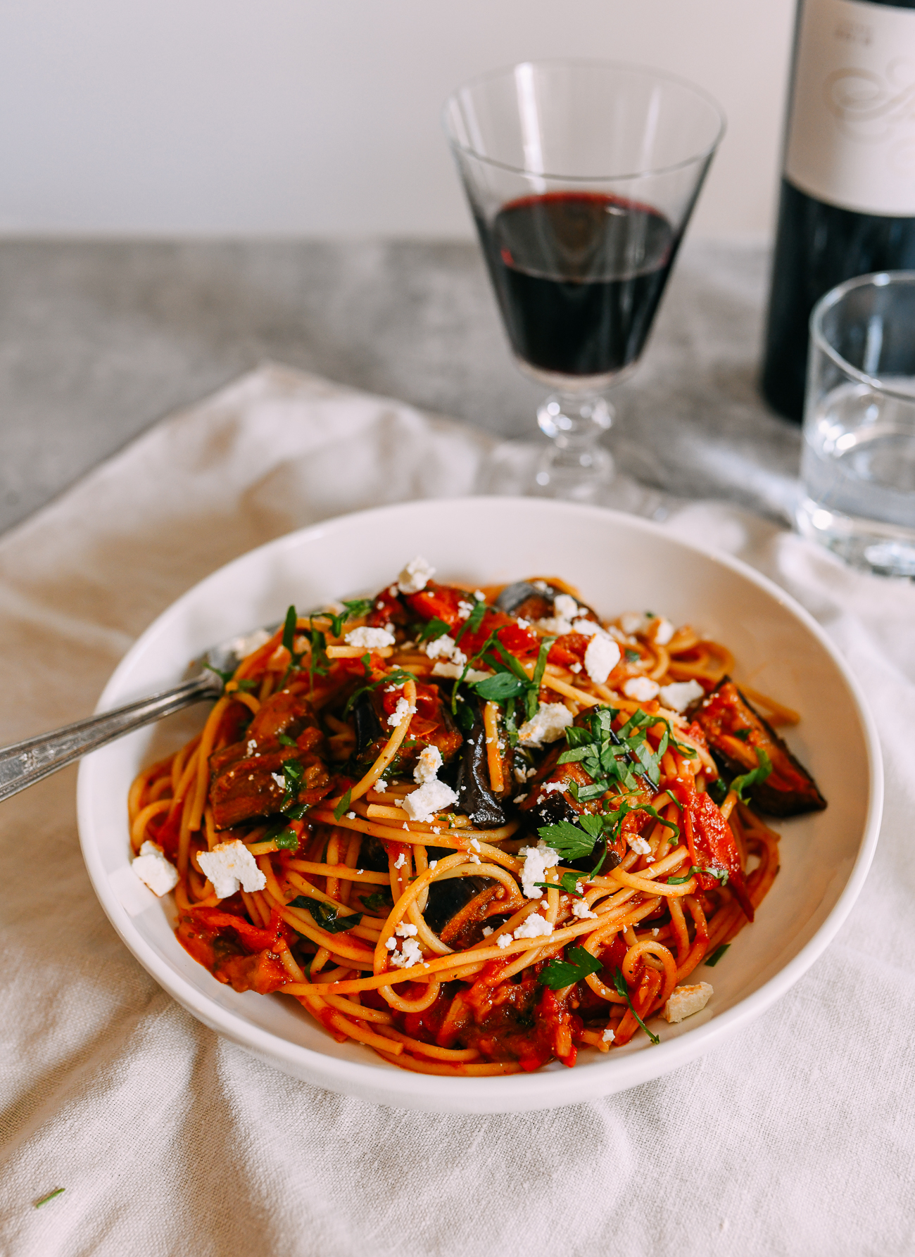 Pasta alla norma served with red wine