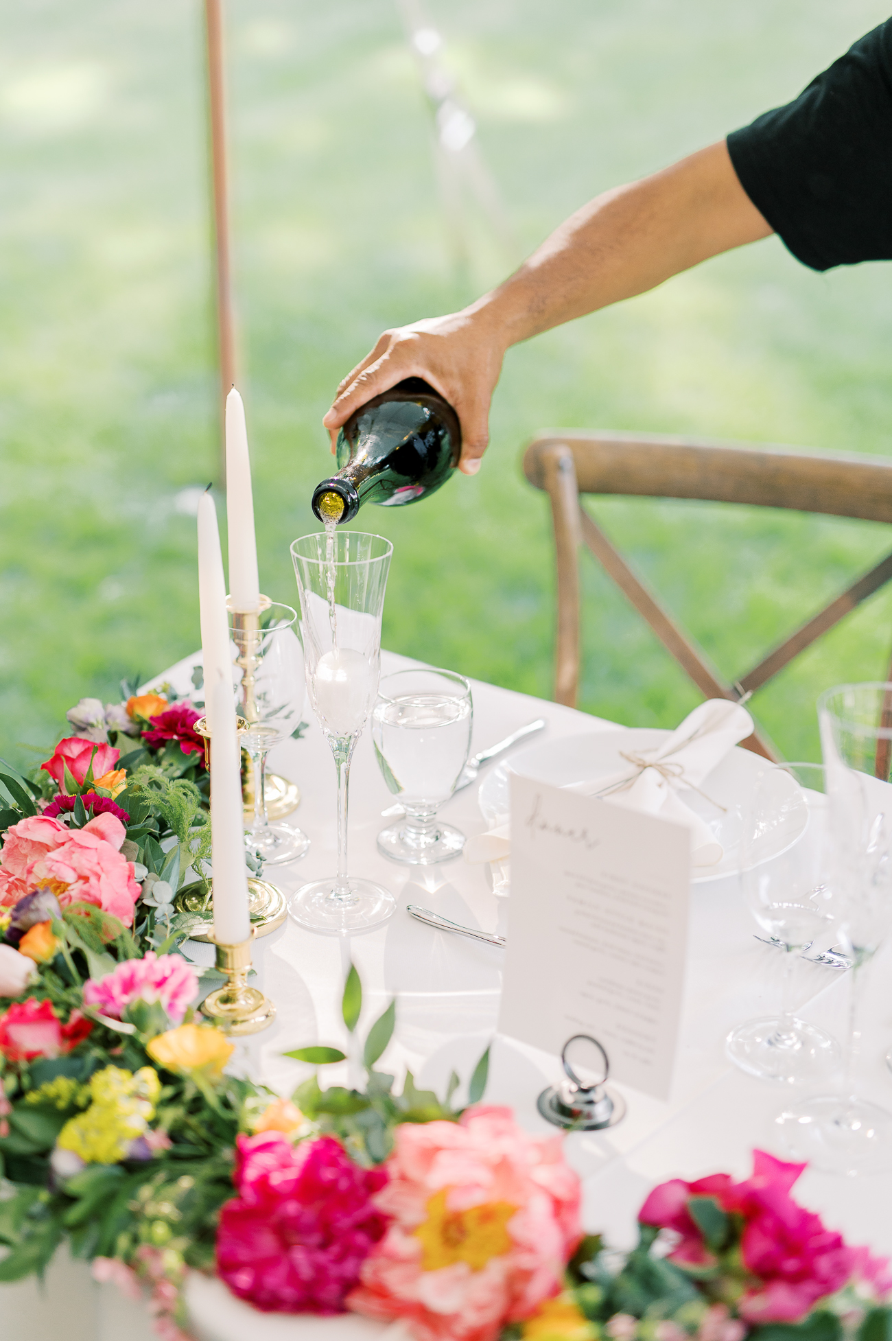 Pouring champagne into toasting glasses at sweetheart table