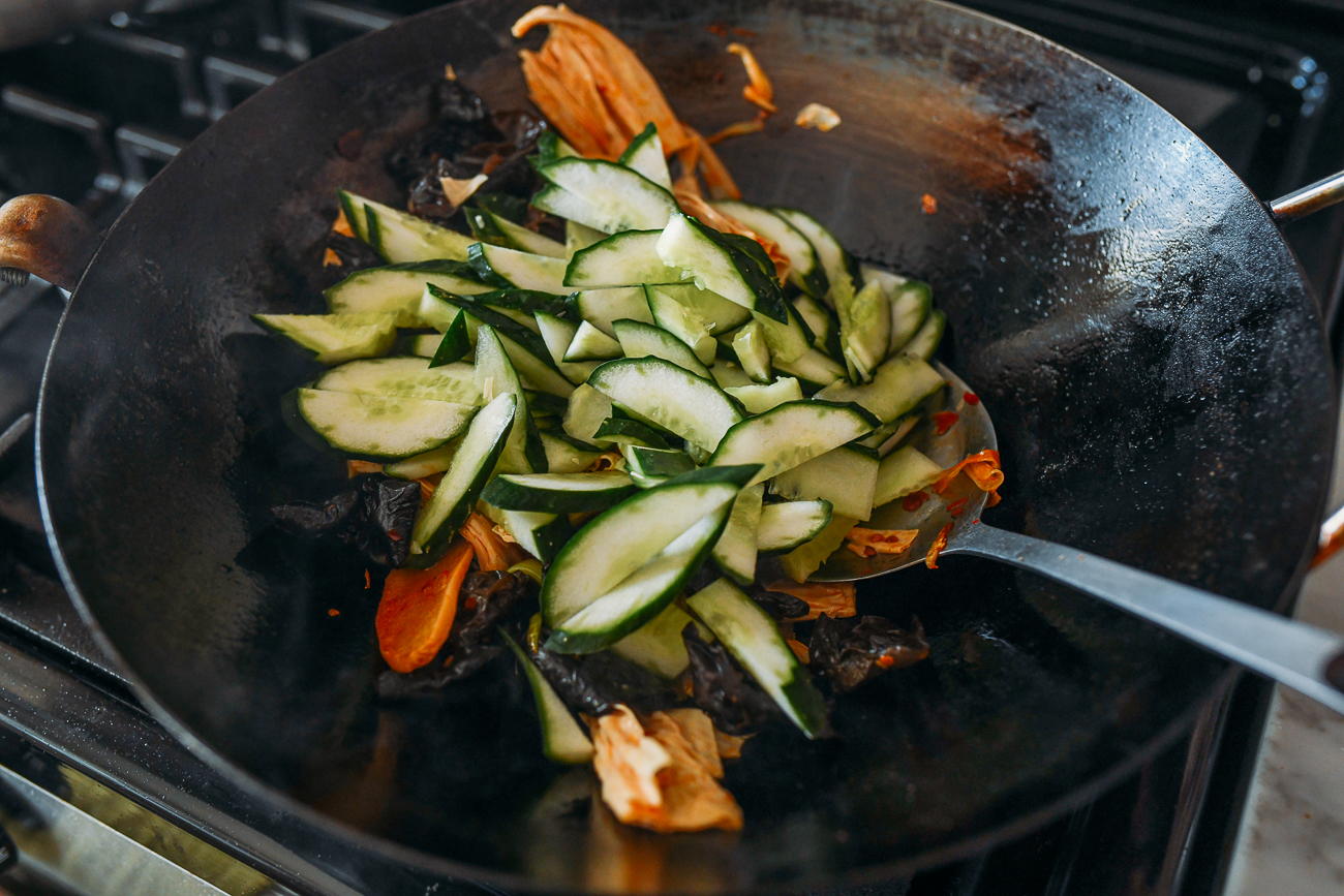 Adding cucumbers to wok