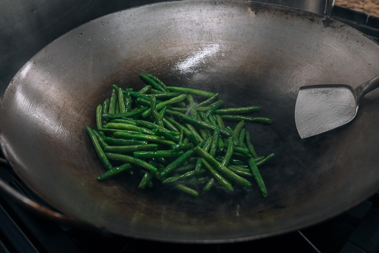 Adding green beans to wok