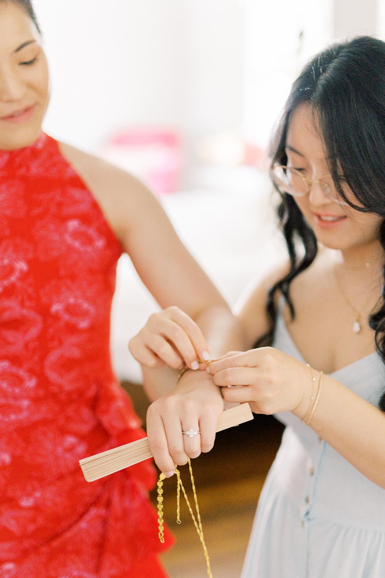 Kaitlin helping Sarah with tea ceremony jewelry