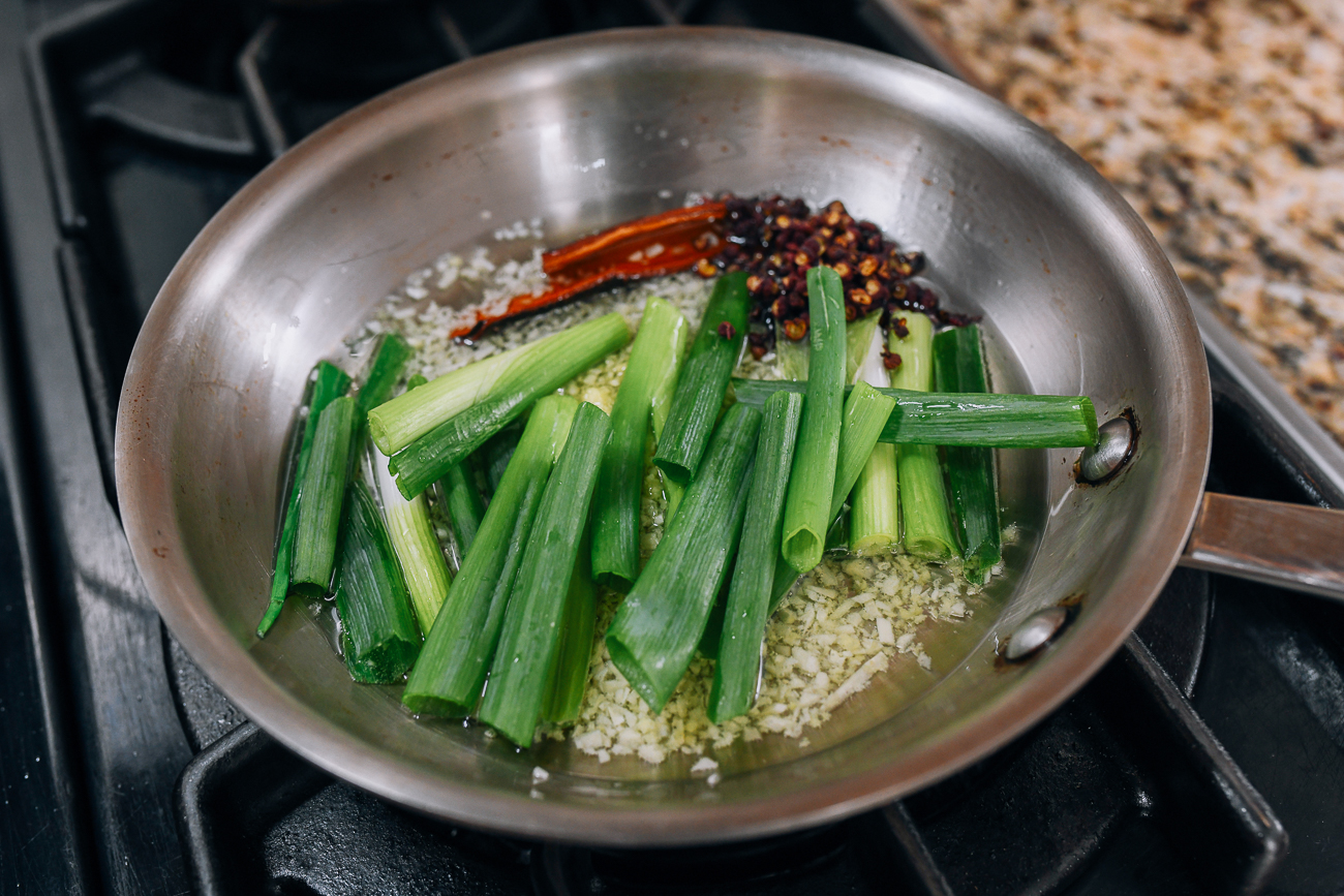 Scallions, garlic, and spices in saucepan with oil
