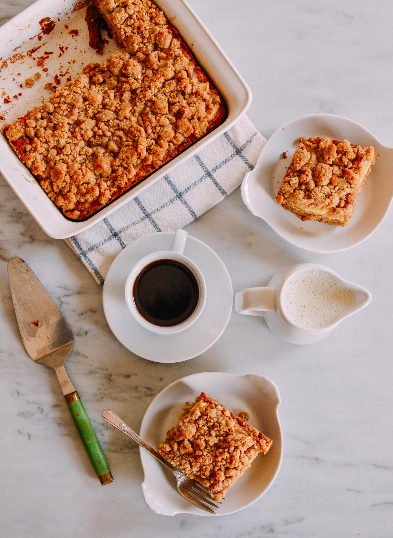 Sliced apple cinnamon coffee cake with cake server and coffee